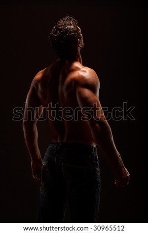 Dramatic image of a beautifully sculpted bodybuilder - stock photo
