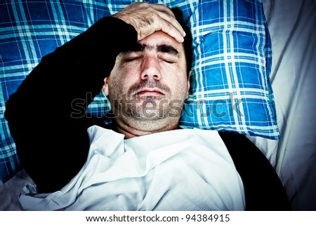 Dramatic image of a very stressed or mentally disturbed man suffering a headache laying in bed - stock photo
