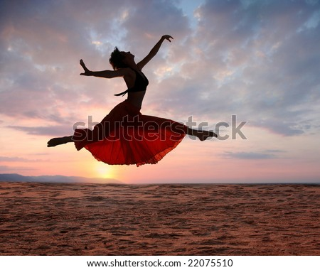 Dramatic image of a woman jumping above the ocean at sunset, silhouette - stock photo