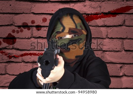 Dramatic image of a young delinquent with a gun suggesting a young terrorist - stock photo