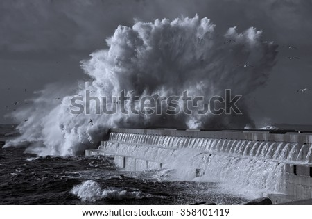 Dramatic image of beacon and south pier of Douro river mouth under heavy storm with big waves. Used infrared filter. Toned blue. - stock photo