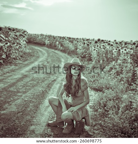 Dramatic image of young traveler woman sitting on a suitcase on rural road. Black and white, grain added, vignette - stock photo