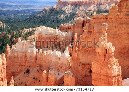 Dramatic landscape at Bryce Canyon National park is decorated with orange sandstone pinnacles, towering over canyon floor, with unique shapes carved by nature's forces - stock photo