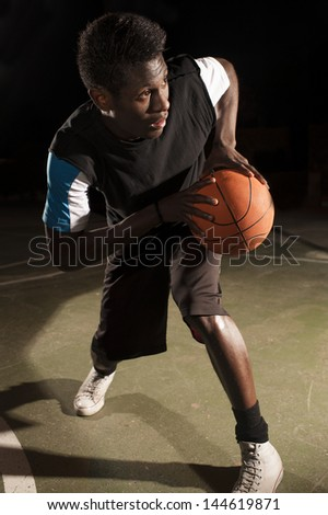 Dramatic light portrait of a African American street basketball player. He is holding the ball during a match - stock photo