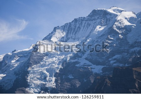 Dramatic light striking snowy and rocky mountainside with deep blue sky - stock photo