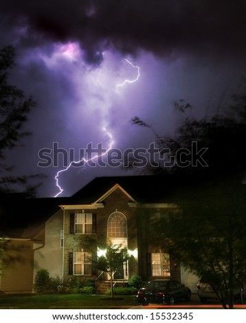 Dramatic lightening storm over suburban home - stock photo