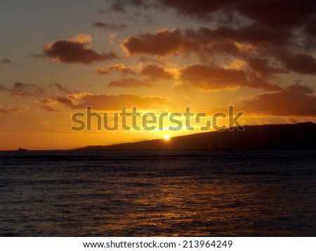 dramatic lighting as Sunsets behind Waianae mountains with light reflecting on ocean and illuminating the sky with boats sailing on the water off Waikiki on Oahu, Hawaii. - stock photo