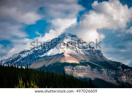Dramatic lighting on a mountain peak with clouds in Banff National Park Alberta Canada.