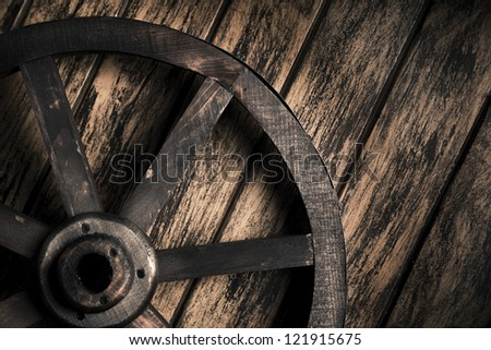 Dramatic lighting on a wood wheel on a grungy background - stock photo