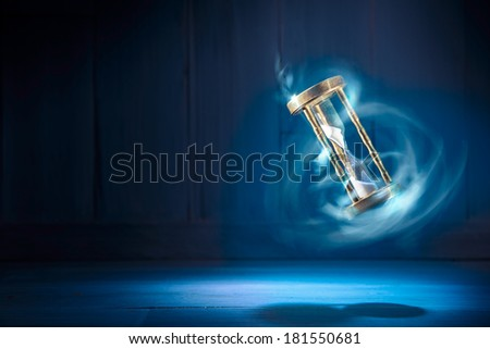 dramatic lit image of hourglass, time concept - stock photo