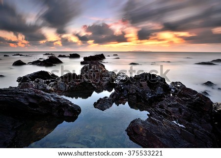Dramatic long exposure seascape during sunset with motion sky. Nature composition. - stock photo