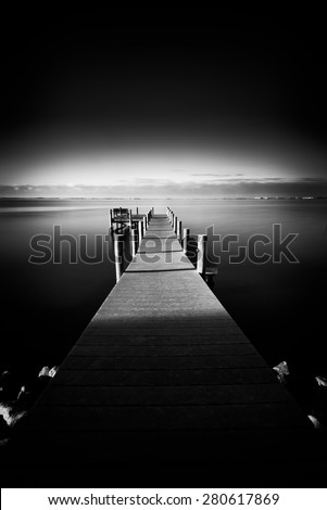 Dramatic long exposure view of a pier resting in the calm waters of the Florida gulf - stock photo