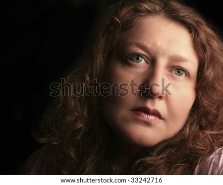 dramatic low-key picture of an attractive middle aged woman