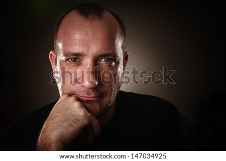Dramatic low-key portrait of adult man looking in camera, closeup. - stock photo