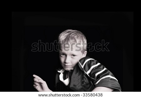 dramatic low key shot of a young blonde boy against a black background