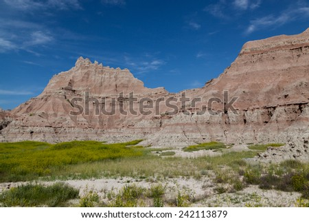 Dramatic mountain formations carved out by erosion showing layers of rocks with spring wildflowers below in Badlands National Park, South Dakota. - stock photo