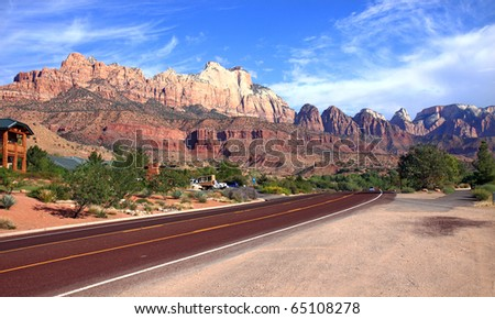 Dramatic mountain scenery along highway through Zion National Park boasts vivid contrasts of red and orange rock formations against vibrant green foliage