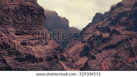 Dramatic mountains sinking in dusk clouds in red planet Mars - stock photo