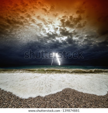 Dramatic nature background - stormy sunset, sea waves, dark sky with lightning - stock photo
