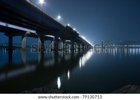 dramatic night view of Seoul city skyline and a bridge - stock photo