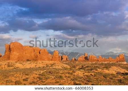 Dramatic panorama shot of arches national park with snow covered mountains in the background