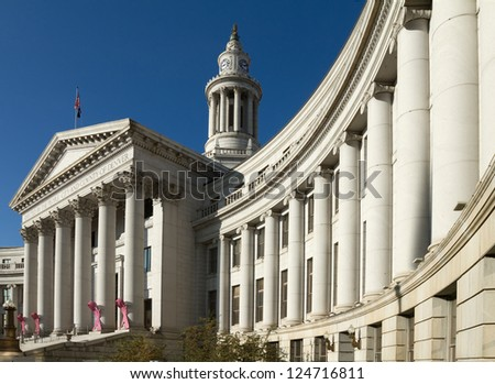 Dramatic perspective of The City and County Building in Denver, Colorado, under a blue sky. The building is adorned with pink Breast Cancer Awareness ribbons. - stock photo