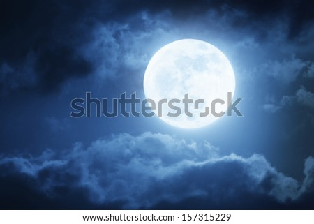 Dramatic photo illustration of a nighttime sky with brightly lit clouds and large, bright full moon would make a great background. - stock photo