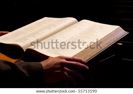 Dramatic photo of a priest reading form the holy bible - stock photo