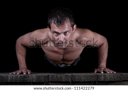 Dramatic portrait isolated on a black background of a young  male doing push-ups - stock photo