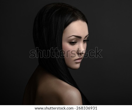 Dramatic portrait of a girl theme: portrait of a beautiful girl on a dark background in studio - stock photo