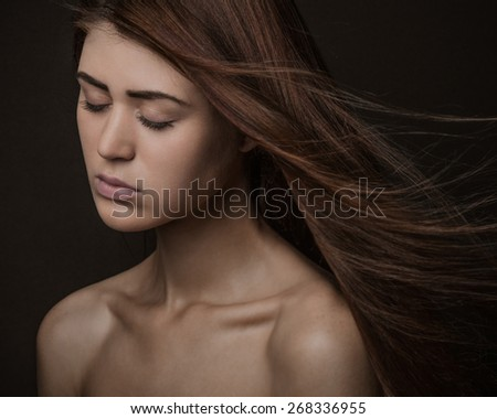 Dramatic portrait of a girl theme: portrait of a beautiful girl with flying hair in the wind against a background in the studio - stock photo