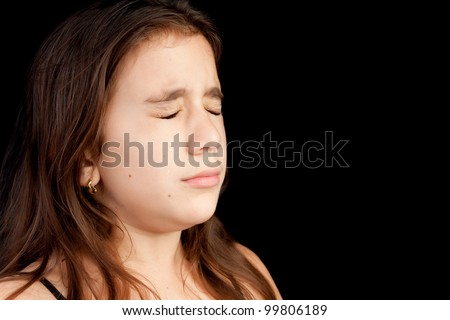 Dramatic portrait of a girl with a very sad face crying isolated on black with space for text - stock photo