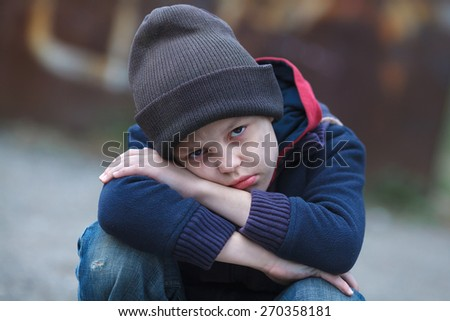 dramatic portrait of a little homeless boy - stock photo