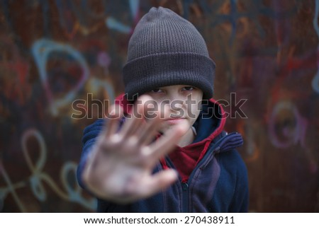 dramatic portrait of a little homeless boy, dirty hand - stock photo