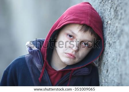 dramatic portrait of a little homeless boy, poverty, city, street - stock photo
