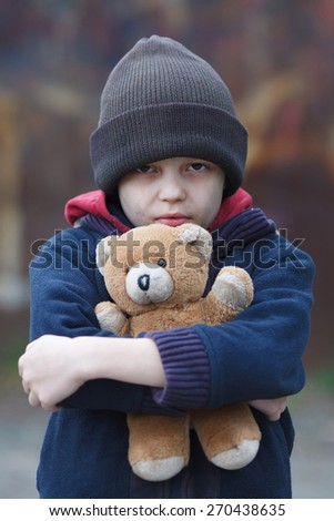 dramatic portrait of a little homeless boy with bear - stock photo