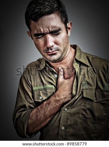 Dramatic portrait of a stressed man suffering from chest pain - stock photo