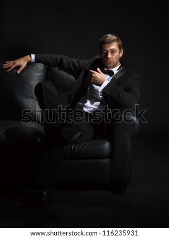 Dramatic portrait of a suave handsome man in a tuxedo and bowtie on couch highlighted in darkness - stock photo