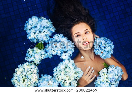 dramatic portrait of a woman floating an a swimming pool full of flowers - stock photo