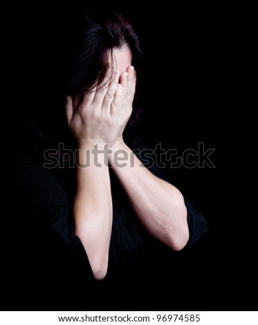 Dramatic portrait of a young woman crying and covering her eyes on a black background with space for text