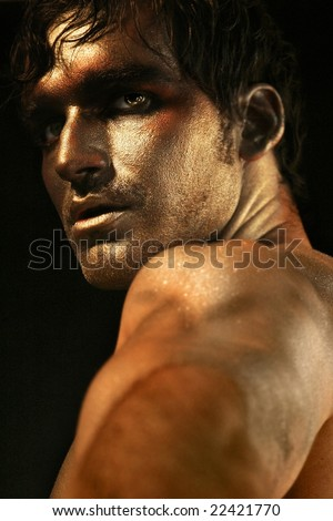 Dramatic portrait of intense looking shirtless male model in bronze and gold makeup turning - stock photo