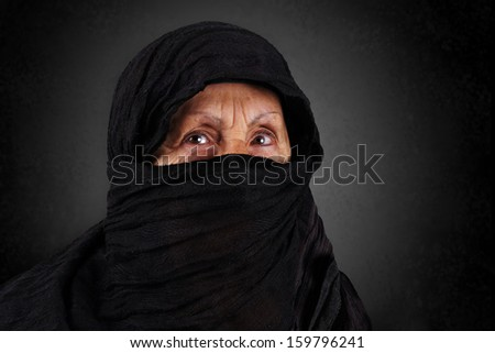Dramatic portrait of senior muslim woman with niqab and hijab - stock photo