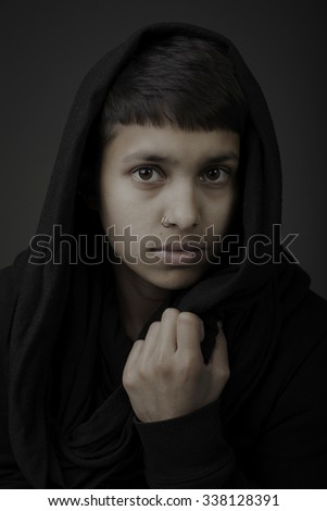 Dramatic portrait of young woman wearing afghan scarf - stock photo
