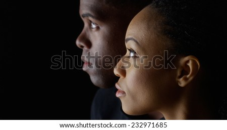 Dramatic profile of Black man and woman looking up - stock photo