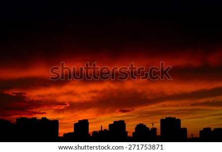 Dramatic red sunset over a dark cityscape.