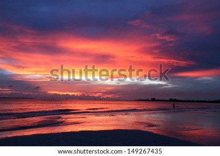 Dramatic red, white and blue beach sunset - stock photo