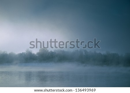 Dramatic river with fog at sunrise with terrible coast - stock photo