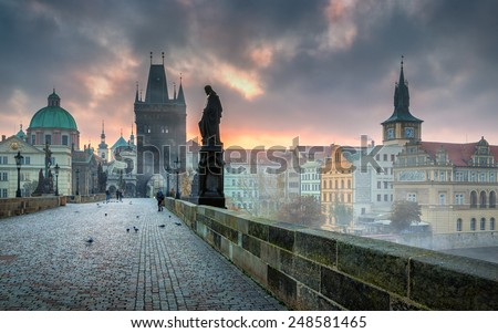 Dramatic scene with cloudy sunrise sky as seen from the Charles bridge in Prague - stock photo