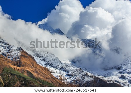 Dramatic sea of clouds and snow covered peaks in Himalaya - stock photo