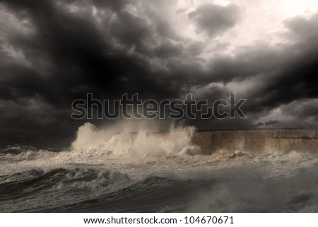 Dramatic sea scene with big white waves crashing against the harbor wall of Leixoes, near Porto in Portugal; enhanced sky; added a little digital grain